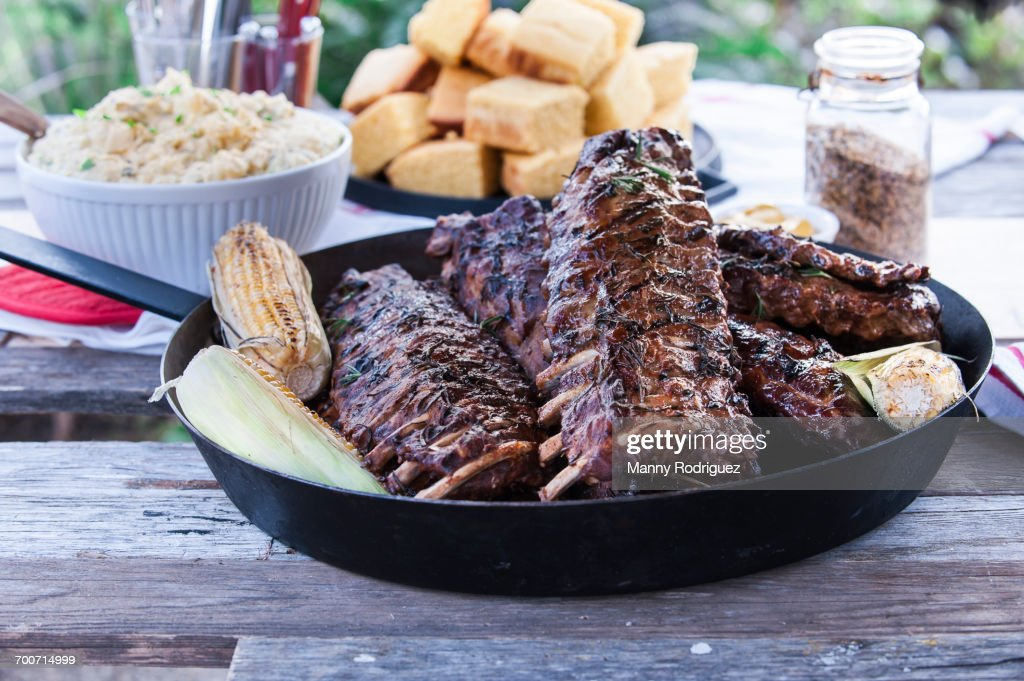 Pan of barbecue ribs on wooden table : Stock Photo