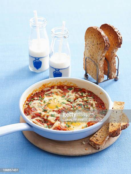 Pan of eggs cooked in sauce with toast