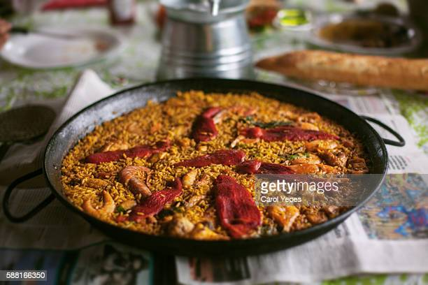 pan of paella on wooden table - paella stock photos and pictures