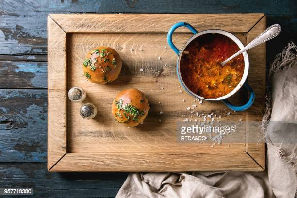 Pan of traditional beetroot borscht soup with sour cream and fresh coriander served with garlic bread buns pampushki on wood tray with textile linen...