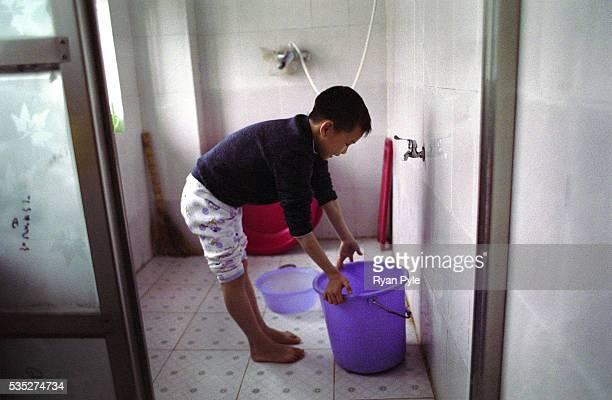 Pan Yi Chao 8 years old washes his feet before his afternoon nap at the Li Xiaoshuang Gymnastics School in Xiantao China Li Xiaoshuang was a...