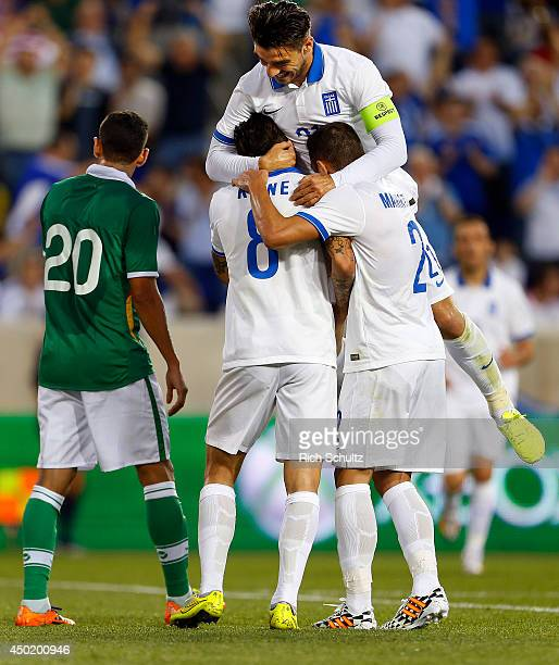 Panagiotis Kone is congratulated by teammates Kostas Katsouranis and Ioannis Maniatis after Kone's goal during the first half of an international...