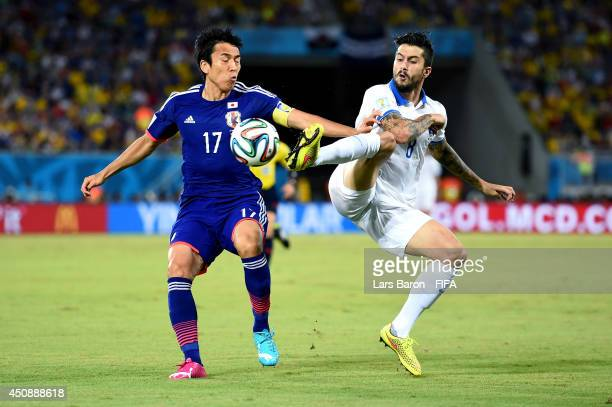 Panagiotis Kone of Greece and Makoto Hasebe of Japan compete for the ball during the 2014 FIFA World Cup Brazil Group C match between Japan and...