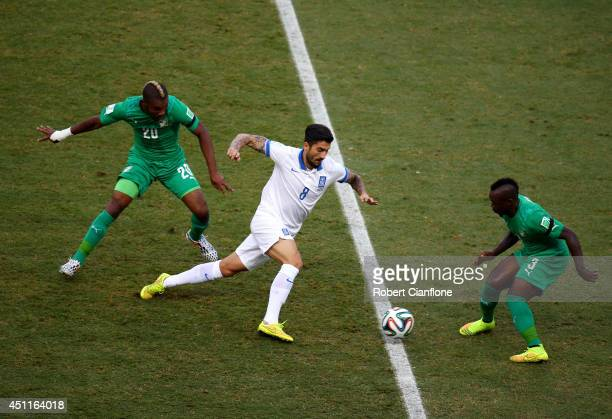 Panagiotis Kone of Greece is challenged by Die Serey and Arthur Boka of the Ivory Coast during the 2014 FIFA World Cup Brazil Group C match between...