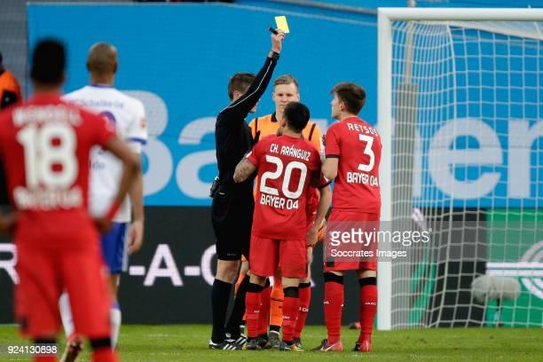 Panagiotis Retsos of Bayer Leverkusen receives a yellow card from referee Daniel Siebert during the German Bundesliga match between Bayer Leverkusen...