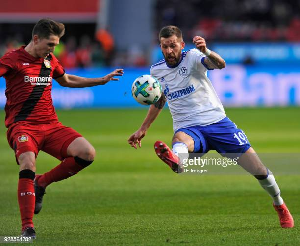 Panagiotis Retsos of Leverkusen and Guido Burgstaller of Schalke battle for the ball during the Bundesliga match between Bayer 04 Leverkusen and FC...