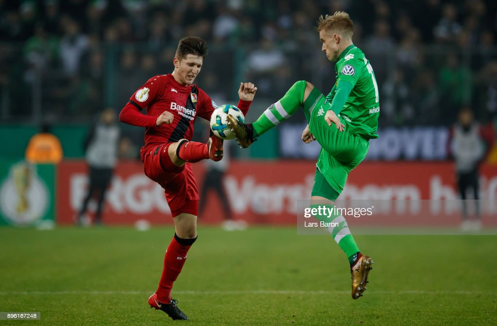 Panagiotis Retsos of Leverkusen challenges Oscar Wendt of Moenchengladbach during the DFB Cup match between Borussia Moenchengladbach and Bayer Leverkusen at Borussia-Park on December 20, 2017 in Moenchengladbach, Germany.