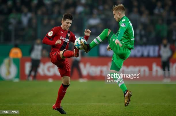 Panagiotis Retsos of Leverkusen challenges Oscar Wendt of Moenchengladbach during the DFB Cup match between Borussia Moenchengladbach and Bayer...