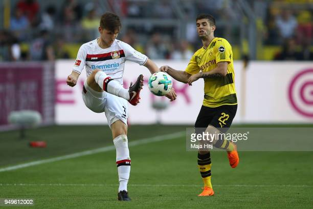 Panagiotis Retsos of Leverkusen fights for the ball with Christian Pulisic of Dortmund during the Bundesliga match between Borussia Dortmund and...
