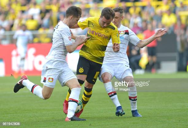 Panagiotis Retsos of Leverkusen Mario Goetze of Dortmund and Dominik Kohr of Leverkusen battle for the ball during the Bundesliga match between...