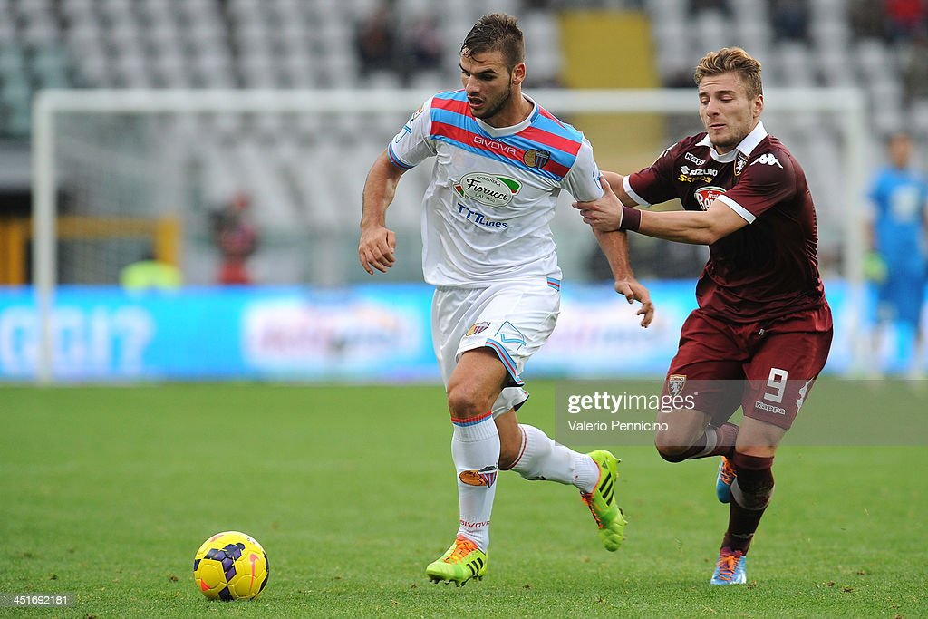 Panagiotis Tachtsidis (L) of Calcio Catania is challenged by Ciro Immobile of Torino FC during the Serie A match between Torino FC and Calcio Catania at Stadio Olimpico di Torino on November 24, 2013 in Turin, Italy.