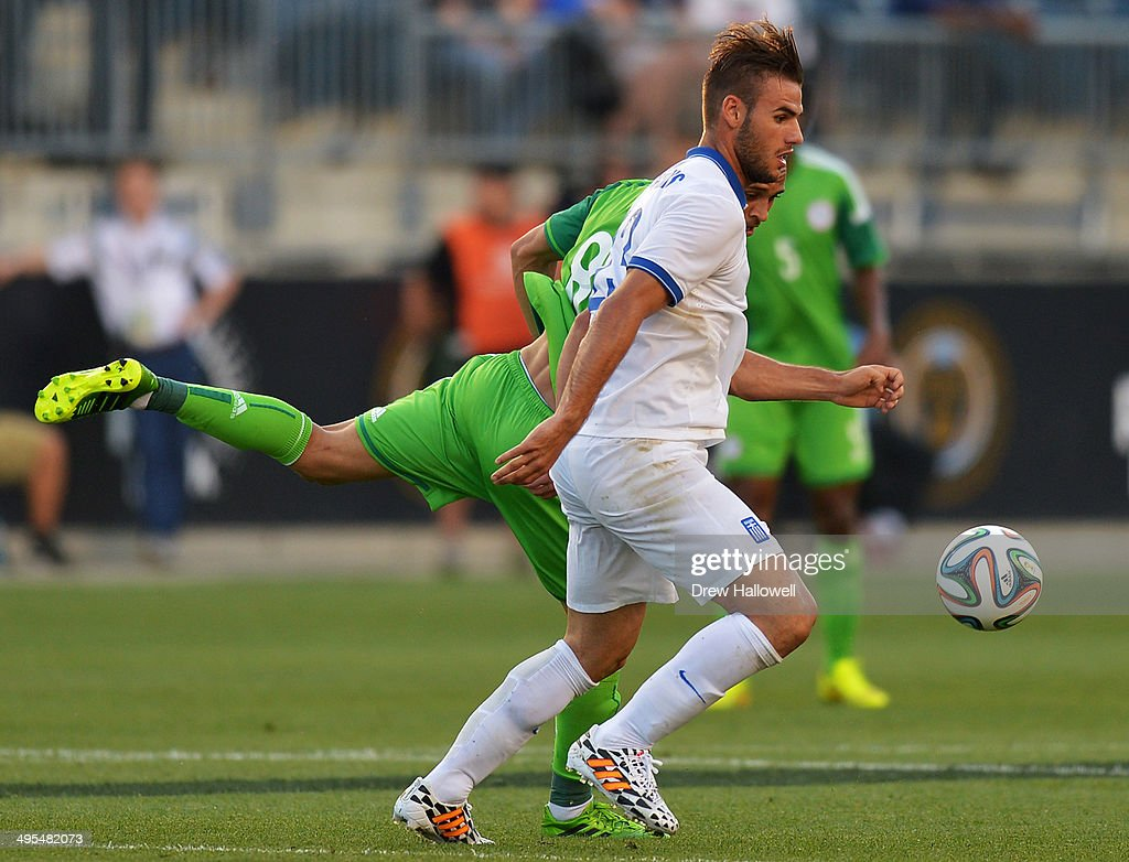 Panagiotis Tachtsidis #23 of Greece and Peter Odemwingie #8 of Nigeria race for the ball during an international friendly match at PPL Park on June 3, 2014 in Chester, Pennsylvania.