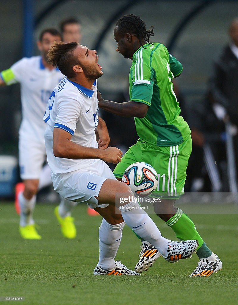 Panagiotis Tachtsidis #23 of Greece and Victor Moses #11 of Nigeria collide during an international friendly match at PPL Park on June 3, 2014 in Chester, Pennsylvania.