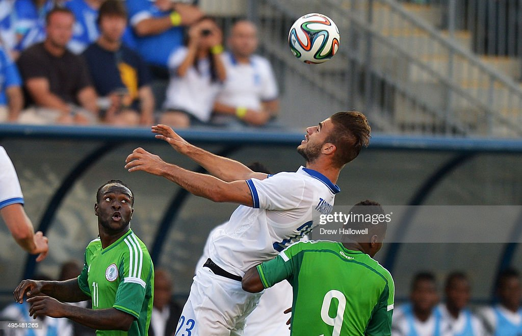 Panagiotis Tachtsidis #23 of Greece heads the ball over Victor Moses #11 and Emmanuel Emenike #9 of Nigeria during an international friendly match at PPL Park on June 3, 2014 in Chester, Pennsylvania.
