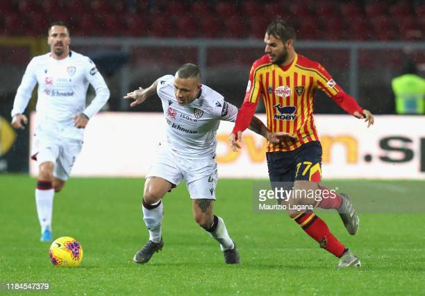 Panagiotis Tachtsidis of Lecce competes for the ball with Radja Nainggolan of Cagliari during the Serie A match between US Lecce and Cagliari Calcio...