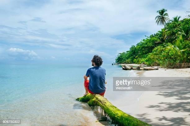 panama, bocas del toro, cayo zapatilla, man sitting on tree trunk on the beach - panama fotografías e imágenes de stock