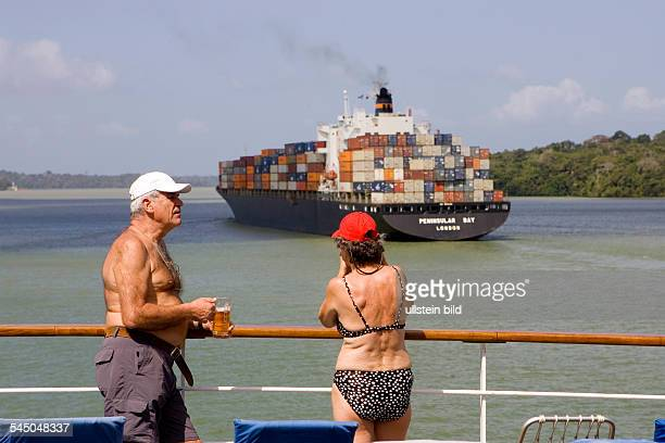 Panama - : Cruise ship MS ASTOR passing the Panama Canal. Party to celebrate the passage. Passengers with a glass of beer standing at the taffrail....