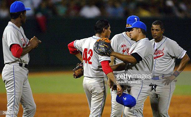 Panamanian Avelisno Aspirilla comforts the opener pitcher Elpidio Pinto after the coach Omar Moreno asked him for the ball at the bottom of the third...