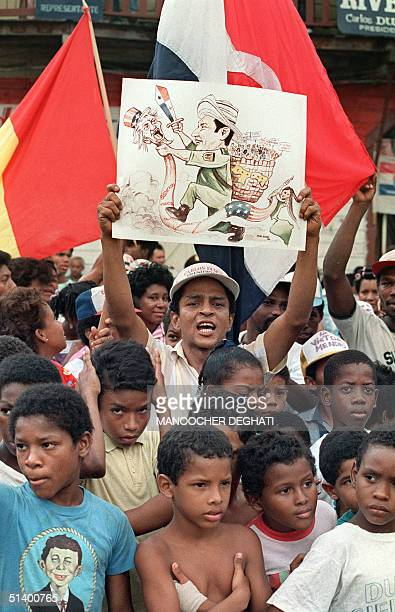Panamanian holds up a sign showing Panamanian leader General Manuel Antonio Noriega attacking a serpent with an 'Uncle Sam' head representing the US...