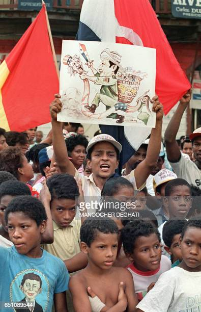 """Panamanian holds up a sign showing Panamanian leader General Manuel Antonio Noriega attacking a serpent with an """"Uncle Sam"""" head, representing the..."""