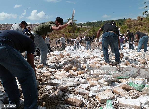 Panamanian policemen smash drug packages with machetes before being incinerated in Cerro Patacon a dump in Panama City on January 18 2012 Panamanian...