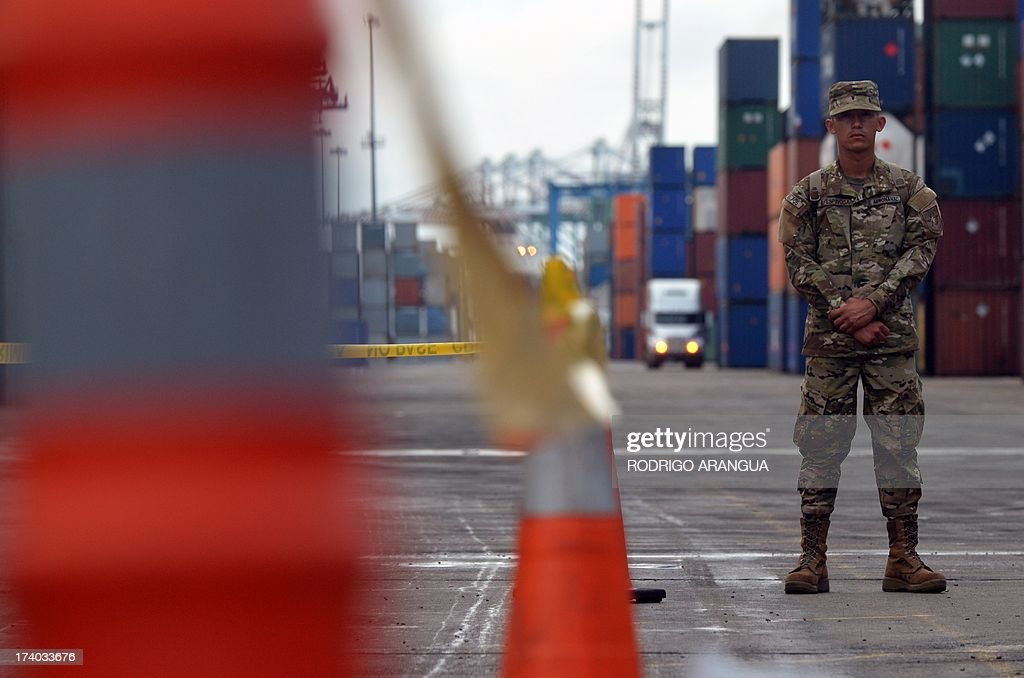 A Panamanian soldier guards containers (out of frame) of the North Korean Chong Chon Gang vessel where an alleged ageing Soviet-built radar control system for surface-to-air missiles was found, at the Manzanillo Port in Colon, 90 km from Panama City, on July 19, 2013. UN sanctions experts will go to Panama soon to investigate a North Korean ship that was intercepted carrying weapons, a US diplomat said Thursday. The vessel set out from Cuba and was trying to enter the Panama Canal when it was stopped by an anti-narcotics patrol, which later found the weapons concealed beneath several tonnes of sugar. AFP PHOTO / Rodrigo ARANGUA
