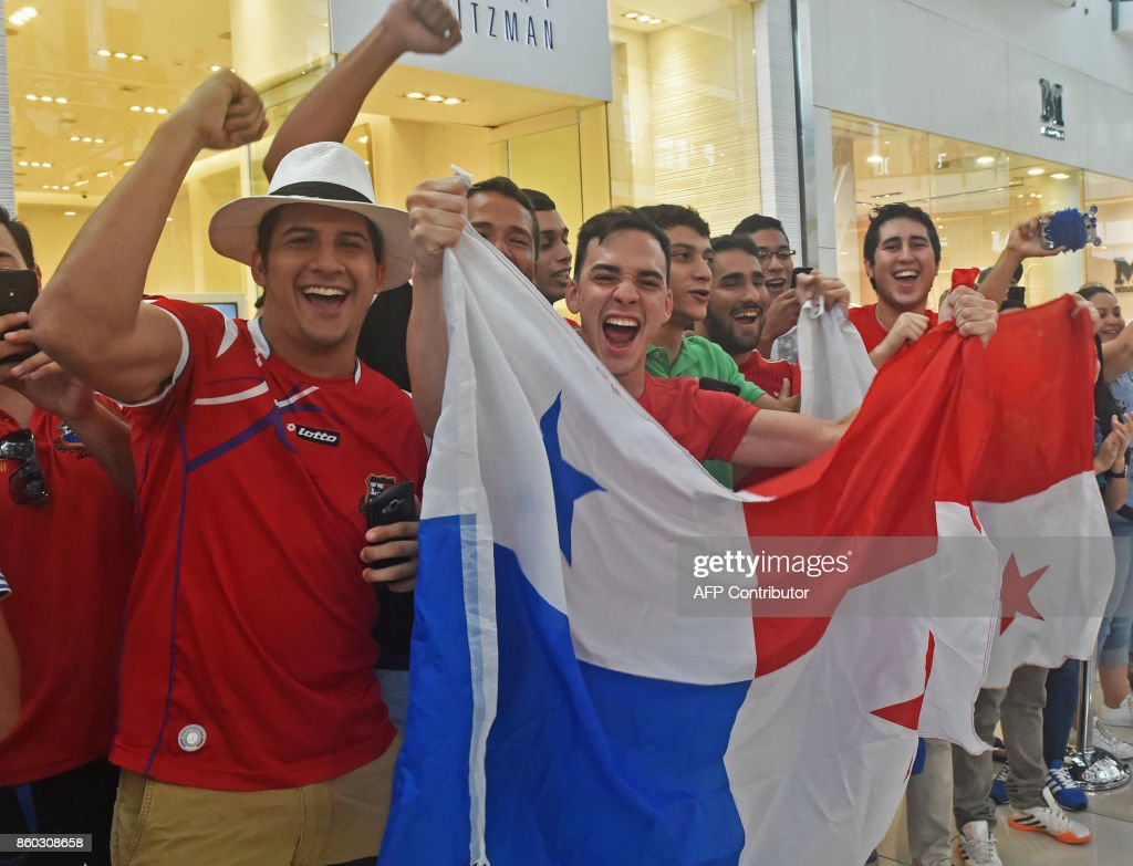 Panama's football team fans wave a national flag and cheer for their team in a mall in Panama City, a day after their national team qualified for the World Cup, for the first time ever, on October 11, 2017. Panama president Juan Carlos Varela declared a national holiday in celebration at the central American country's first ever qualification for the World Cup. /