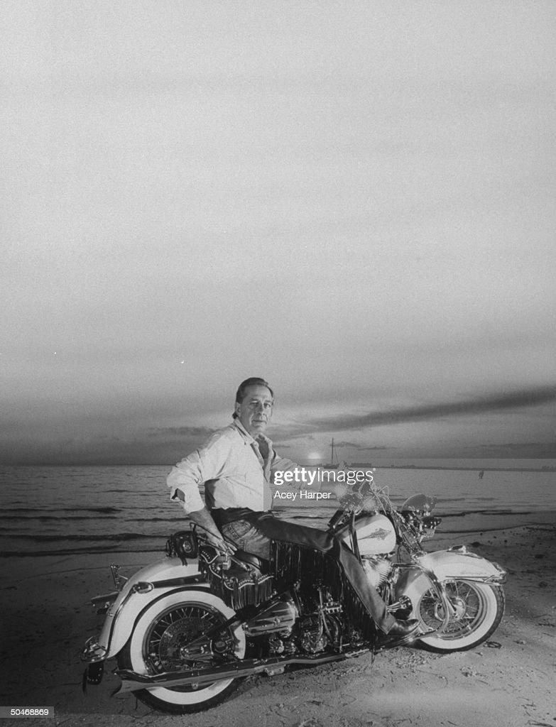 Panama's Gen. Manuel Noriega's defense attorney Frank Rubino riding on his Harley-Davidson on beach at sunset.