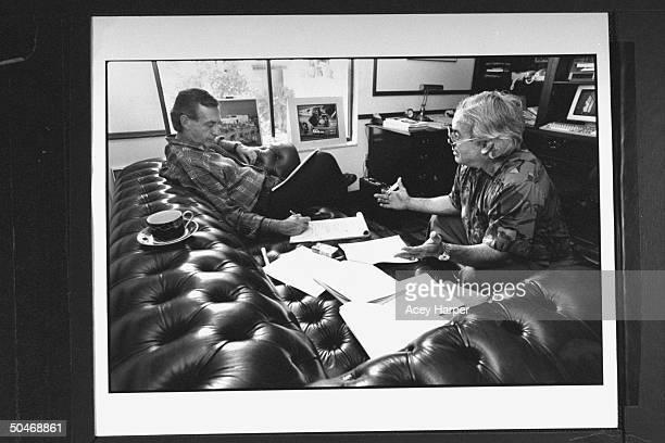 Panama's Gen Manuel Noriega's defense attorney Frank Rubino sitting on sofa working on case w investigator Jack Fernandez in study of Rubino's home