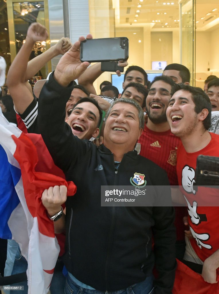 Panama's national football coach Hernan Dario Gomez (C) takes a selfie picture with supporters in a mall in Panama City, a day after their national team qualified for the World Cup, for the first time ever, on October 11, 2017. Panama president Juan Carlos Varela declared a national holiday in celebration at the central American country's first ever qualification for the World Cup. /