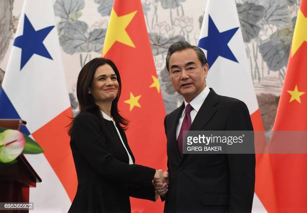 Panama's Vice President and Foreign Minister Isabel de Saint Malo shakes hands with Chinese Foreign Minister Wang Yi during a joint press briefing...