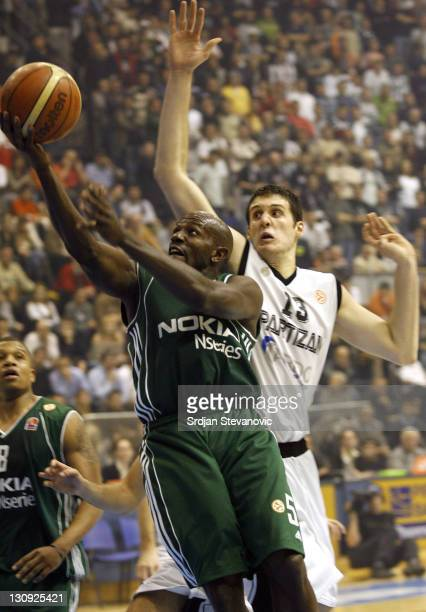 Panathinaikos Athens player Tony Delk, left, try to score near Kosta Perovic, right, from Partizan during their group B Euroleague basketball match...