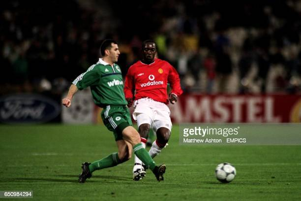 Panathinaikos' Ioannis Goumas passes the ball under pressure from Manchester United's Dwight Yorke