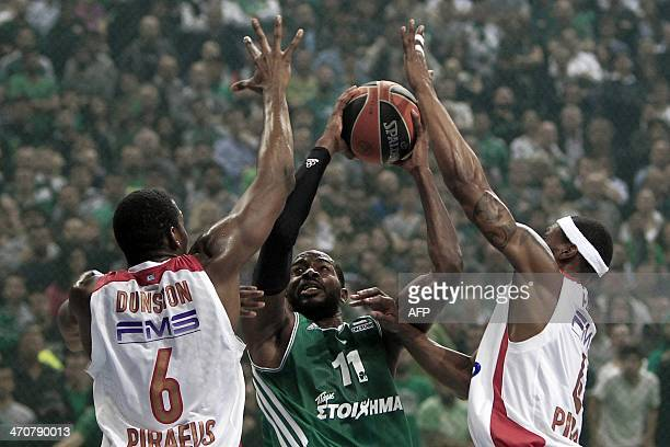 Panathinaikos' Lasme Stephane tries to scores in front of Olympiakos' players Bryant Dunston and Brent Petway during the Top 16 Euroleague basketball...