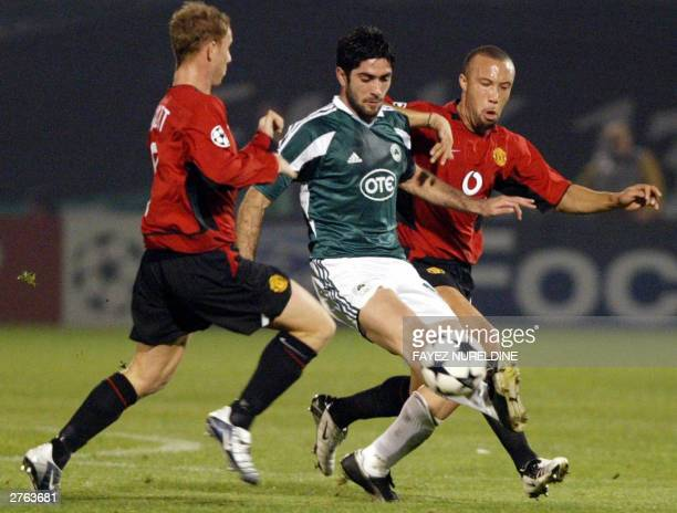 Panathinaikos' Michalis Konstantinou controls the ball as Manchester United's Mikael Silvestre and Nicky Butt try to stop him during their Champions...