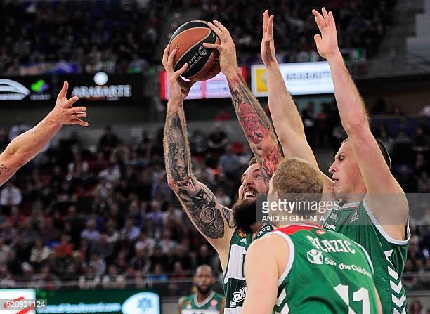 Panathinaikos' Serbian center Miroslav Raduljica vies with Laboral Kutxa's Slovenian guard Jaka Blazic and teammate Croatian center Darko Planinic...