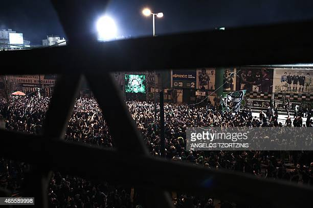 Panathinaikos' supporters watch on a screen in a street of Athens a football match between Panathinaikos and Paok Thessaloniki on March 8 after the...