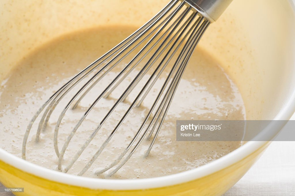 Pancake batter and whisk in mixing bowl : Stock Photo