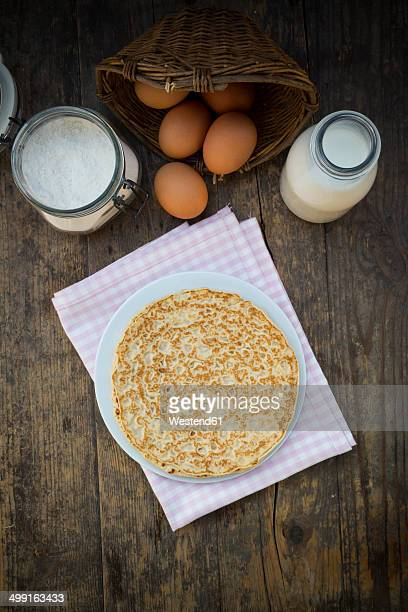 Pancake on plate and ingredients, eggs, milk and flour