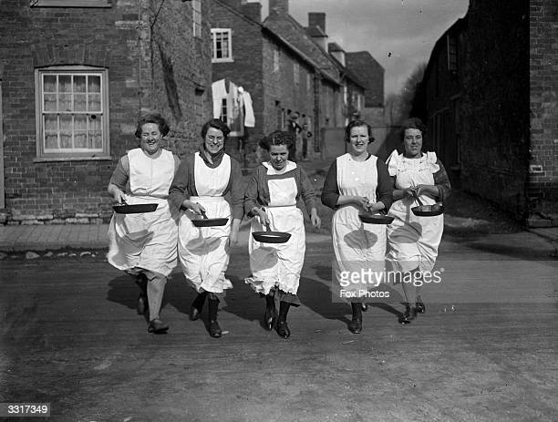 A pancake race at Olney an old English custom in the village