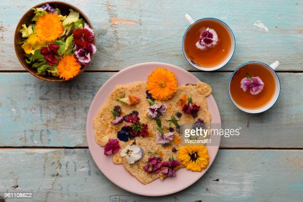 Pancake with edible flowers, pumpkin flower, Calendula, Chamaemelum nobile, Dianthus, Taraxacum officinale, Viola, Rosmarinus officinalis on bamboo plate and cups of tea