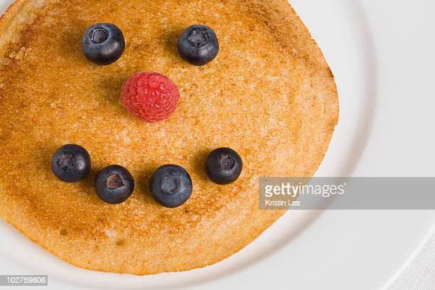 Pancake with smiley face made from blueberries and raspberry