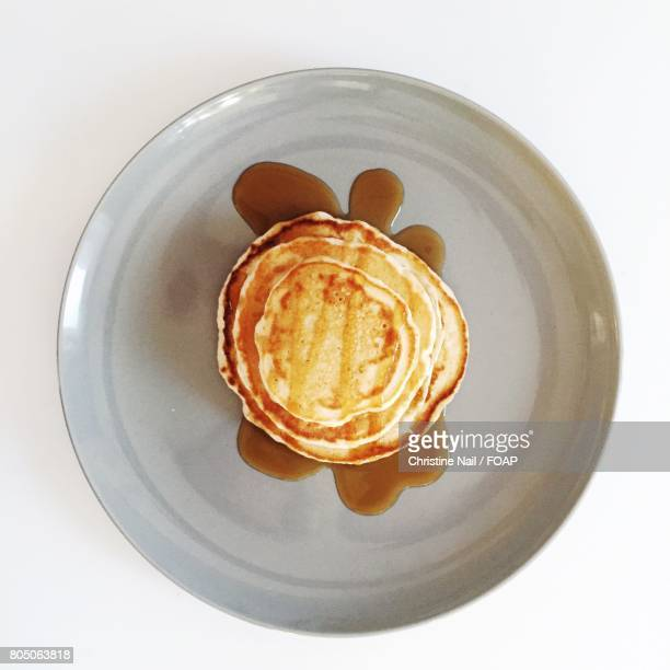 Pancake with syrup on plate against white background