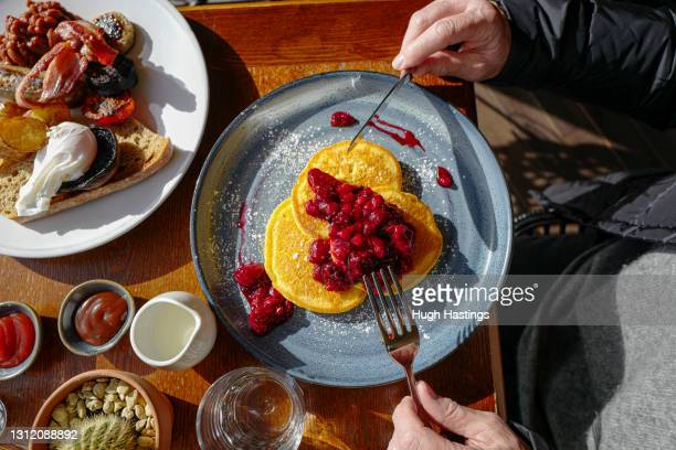 Pancakes and berries breakfast on the terrace at the Indidog brasserie, as outdoor hospitality restarts on April 12, 2021 in Falmouth, England....