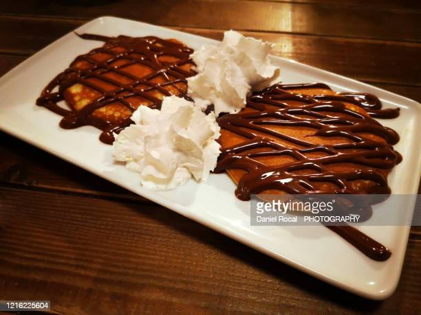 pancakes covered with chocolate and cream - nutella stock pictures, royalty-free photos & images
