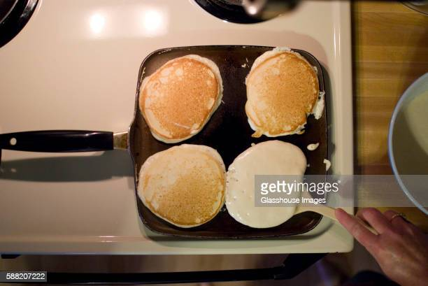 Pancakes on Skillet, One being Flipped