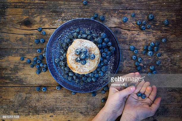 Pancakes with blueberries on plate and girls hands