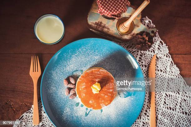 Pancakes with milk, honey and almonds on blue plate for breakfast food on wooden table background.