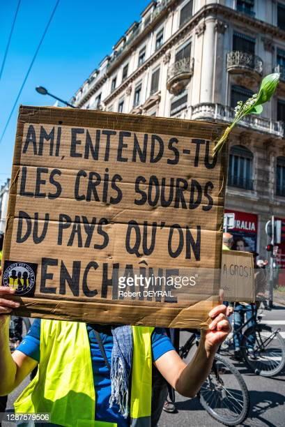 """Pancarte """"Ami entends-tu les cris sourds d'un pays qu'on enchaine"""" portée par un manifestant gilet jaune et muguet lors de la manifestation du 1er..."""