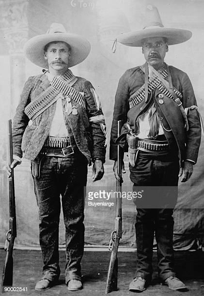 Pancho Villa's Men Urbino Iluarte stand at attention with rifles bandoliers and Pistols